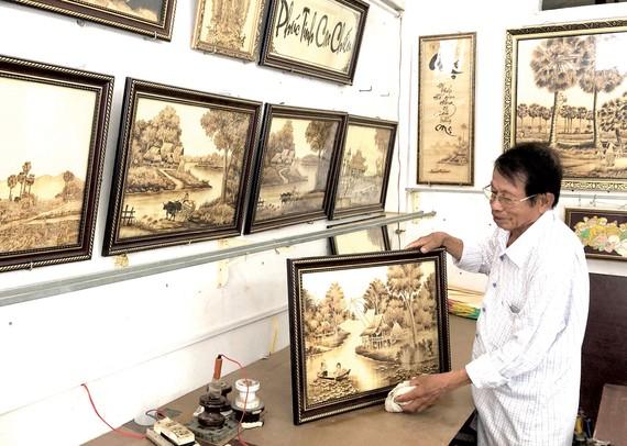 Nghệ nhân Võ Văn Tạng giới thiệu những bức tranh bằng lá thốt nốt