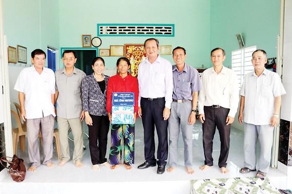 Ông Lưu Hoàng Tân - Chủ tịch, Giám đốc Công ty TNHH MTV Xổ số kiến thiết Đồng Tháp (thứ năm từ trái sang trao nhà tình thương cho hộ gia đình chính sách)