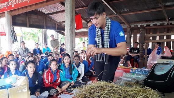Chiến sĩ tình nguyện Mùa hè xanh tập huấn cách trồng nấm cho người dân,  thanh niên nước bạn Lào. Ảnh: THU HƯỜNG