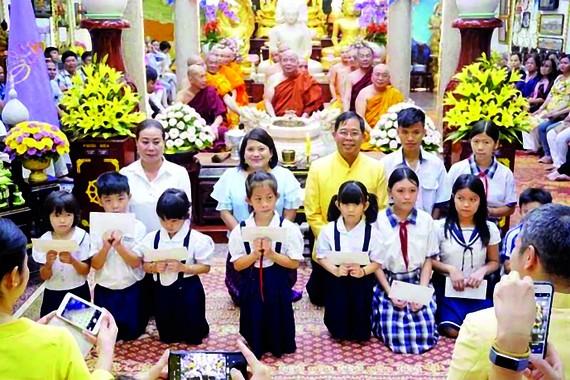 Tổng Lãnh sự Thái Lan tại TPHCM Apirat Sugondhabhirom (áo vàng)  trao học bổng cho học sinh nghèo tại chùa Phổ Minh (TPHCM)