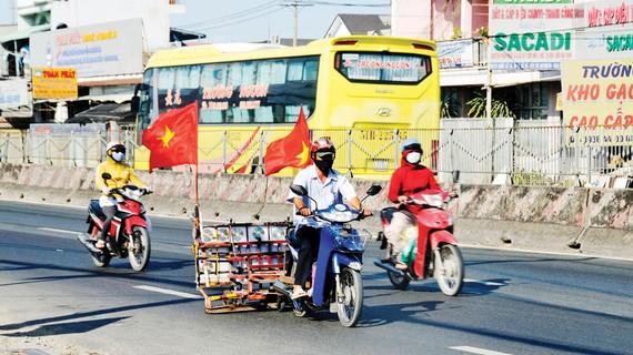Người dân sử dụng xe máy hút đinh trên quốc lộ 1A đoạn qua huyện Bình Chánh, TPHCM. Ảnh: CAO THĂNG