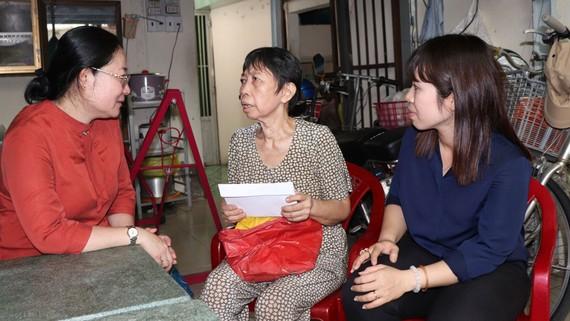 Đảng viên trên địa bàn quận 8 thăm hỏi và trao hỗ trợ cho bà Cổ Thị Thâm (giữa)  thời điểm tháng 6-2020. Ảnh: THÁI PHƯƠNG