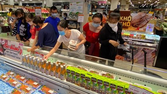 Người tiêu dùng mua thực phẩm khuyến mãi tại siêu thị Aeon Mall Bình Tân. Ảnh: CAO THĂNG