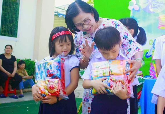 Cô Nguyễn Thị Thu Hà, Giám đốc Trung tâm Nuôi dạy trẻ khuyết tật Võ Hồng Sơn, trao quà cho trẻ khuyết tật