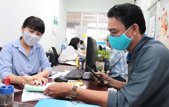 Nhân viên Công ty CP Cấp nước Bến Thành hướng dẫn người dân  thực hiện các thủ tục hành chính