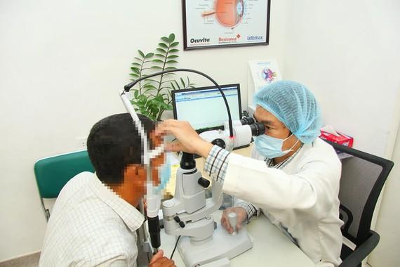 Bác sĩ Trần Hiếu đang thăm khám cho bệnh nhân biến chứng mắt do đái tháo đường