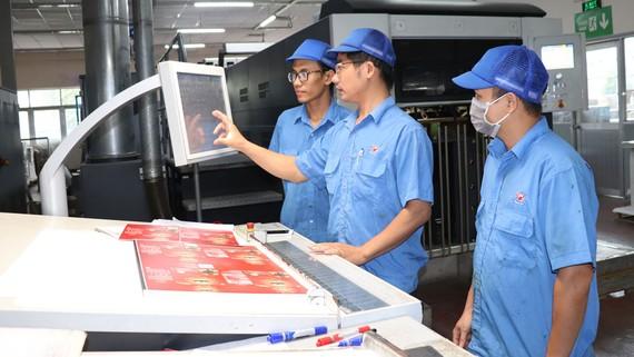 Nhờ cách đào tạo tại Công ty cổ phần In số 7, Lương Ngọc Thẩm (giữa) từ vị trí số 3 đã lên làm trưởng máy in thế hệ mới và được đi học tập tại Nhật. Ảnh: THÁI PHƯƠNG