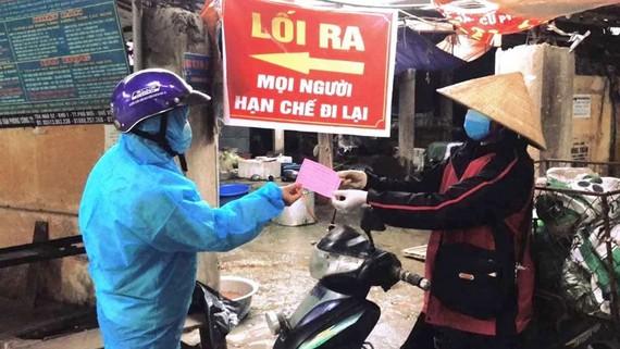 Các tiểu thương tại chợ ở TP Chí Linh được phát phiếu kinh doanh luân phiên. Ảnh: THANH HƯNG