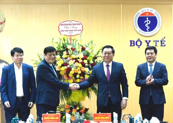 Thượng tướng Nguyễn Trọng Nghĩa, Bí thư Trung ương Đảng, Trưởng ban Tuyên giáo Trung ương tặng hoa cho Bộ trưởng Bộ Y tế Nguyễn Thanh Long. Ảnh: VGP