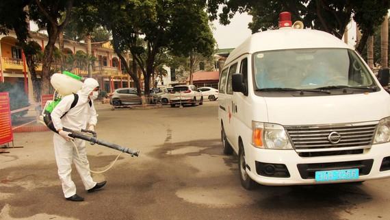 Lực lượng chức năng tiến hành phun thuốc khử khuẩn phương tiện vận chuyển bệnh nhân mắc Covid-19 tại Trung tâm Y tế Chí Linh, Hải Dương