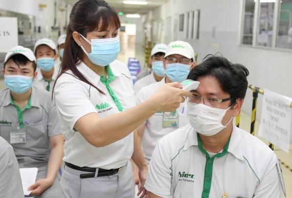 Đo thân nhiệt trước khi tiêm vaccine Covid-19cho nhân viên Công ty Nidec (Khu công nghệ cao TPHCM). Ảnh: HOÀNG HÙNG