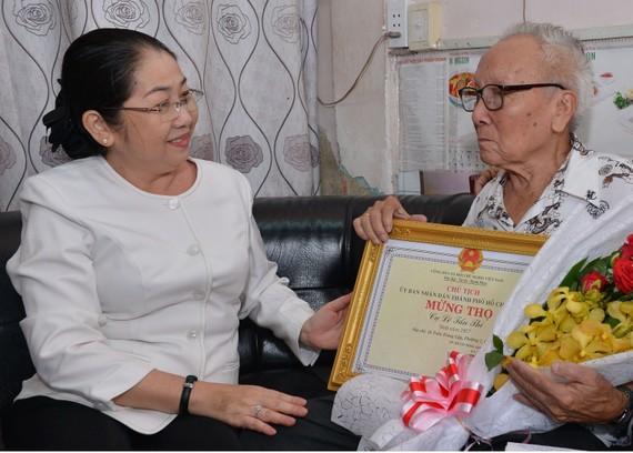 Phó Bí thư Thành ủy TPHCM Võ Thị Dung chúc mừng cụ Lê Tấn Thi, 91 tuổi, cán bộ hưu trí, ngụ phường 2 (quận 6). Ảnh: Việt Dũng