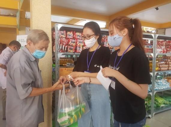 Các tình nguyện viên chọn hàng theo phiếu và trao tận tay cho người đi mua hàng
