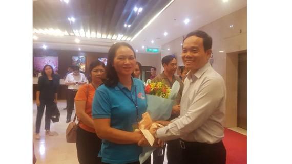 Đồng chí Trần Lưu Quang tặng hoa chúc mừng đoàn đại biểu già làng, trưởng bản tiêu biểu tỉnh Cao Bằng đến TPHCM