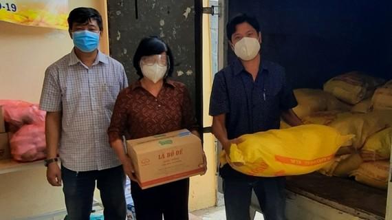 Đại diện lãnh đạo UBND phường 14, quận 8 tiếp nhận 2 tấn gạo và 200 chai nước tương từ Chuyến xe yêu thương
