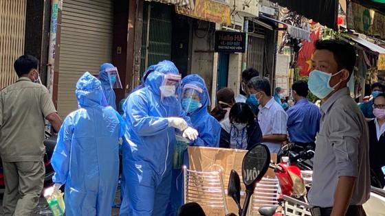 Nhân viên y tế tiến hành lấy mẫu xét nghiệm các trường hợp tiếp xúc gần ca dương tính SARS-CoV-2 ở quận 3, trưa 20-5-2021. Ảnh: CAO THĂNG