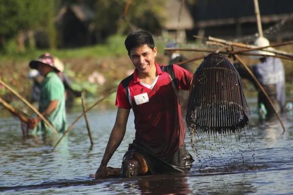 Sau tiếng kẻng báo hiệu, hàng trăm người nông dân cùng đổ xuống trằm để tham gia bắt cá