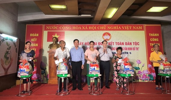 Bí thư Quận ủy quận 5 Nguyễn Văn Hiếu và Chủ tịch Ủy ban MTTQ Việt Nam quận 5 Lê Tấn Tài trao quà cho các gia đình có hoàn cảnh khó khăn. Ảnh: MAI HOA