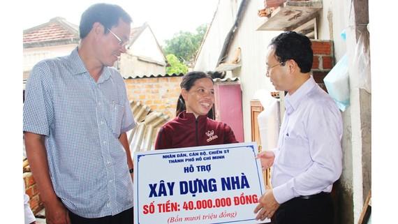 Đồng chí Nguyễn Văn Hiếu  trao tiền hỗ trợ xây nhà cho chị Hồ Thị Bông, ở xã Phước Sơn (huyện Tuy Phước, Bình Định)