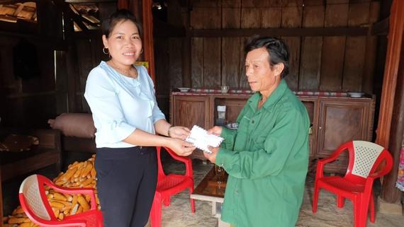Bà Cao Thị Hoa, Phó Chủ tịch UBND xã Minh Hóa, thay mặt bạn đọc Báo SGGP trao số tiền 10 triệu đồng đến cựu binh Trương Văn Thanh