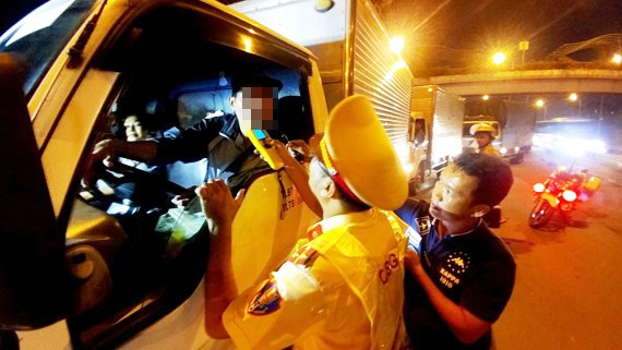 Cảnh sát giao thông TPHCM kiểm tra nồng độ cồn một tài xế xe tải trên Quốc lộ 1A. Ảnh: TUẤN VŨ