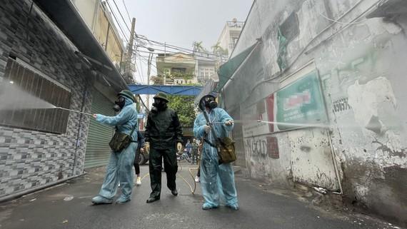 Phun khử khuẩn trong hẻm đường Nguyễn Văn Công, phường 3, quận Gò Vấp vào chiều 1-6. Ảnh: VĂN MINH