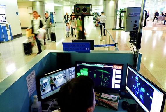 Kiểm tra thân nhiệt hành khách nhập cảnh tại các sân bay. Ảnh: HOÀNG HÙNG