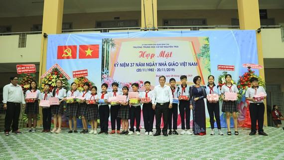Ban đại diện hội phụ huynh học sinh Trường THCS Nguyễn Trãi quận Bình Tân và đại diện các nhà tài trợ tặng học bổng và quà cho các em học sinh nghèo hiếu học.