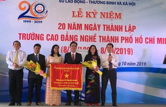 Ông Lê Minh Tấn, Giám đốc Sở LĐTB-XH TPHCM ( ngoài cùng bên trái) đại diện UBND TPHCM trao bức trướng của UBND TPHCM cho Ban Giám hiệu nhà trường