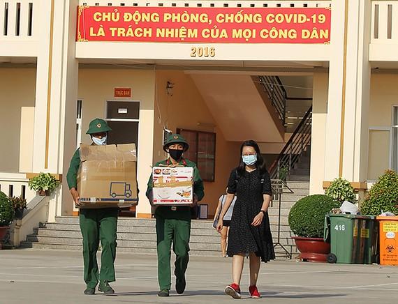 Các chiến sĩ Sư đoàn 317 giúp công dân đưa hành lý ra xe. Ảnh: HOÀNG HÙNG