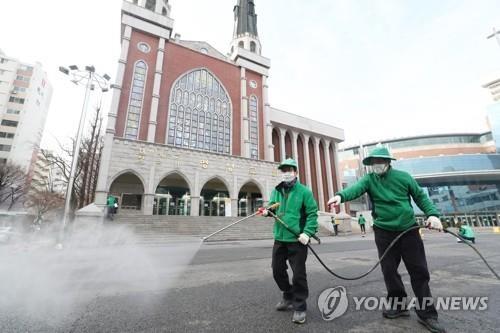 Công nhân khử trùng một khu vực xung quanh nhà thờ Myungsung, một nhà thờ có 80.000 tín đồ, tại Seoul, ngày 26-2, sau khi một mục sư của nhà thờ xét nghiệm dương tính với chủng mới của virus Corona. Ảnh: Yonhap