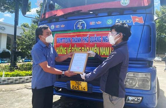 Đại diện UBMTTQ TP Quảng Ngãi (trái) trao quà cho đại diện người dân Quảng Ngãi tại TPHCM.