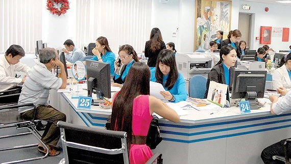 Clients do transactions at a bank in Ho Chi Minh City. (Photo: SGGP)