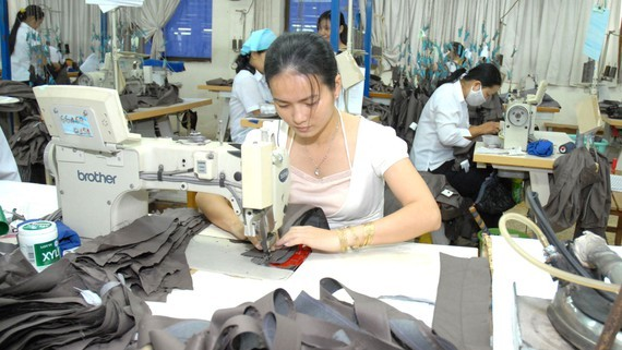 Workers make suit jackets for export. (Photo: SGGP)