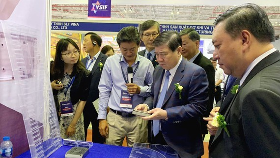 Mr. Nguyen Thanh Phong, chairman of HCMC People's Committee, visits a stall of a Vietnamese supporting industry enterprise at the exhibition. (Photo: SGGP)
