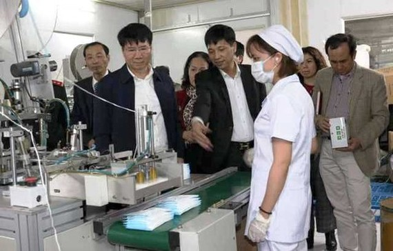 A delegation from the Ministry of Health visits a medical face mask manufacturer. (Photo: SGGP)