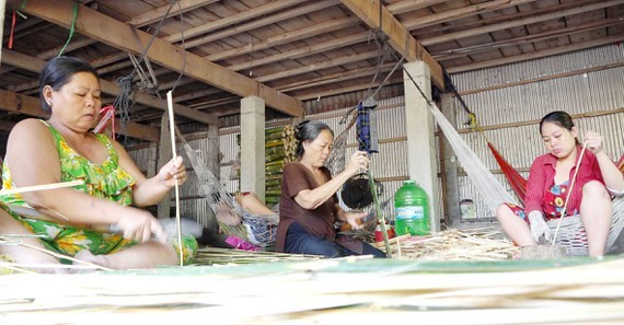 Farmers in Hong Ngu Town in Dong Thap Province are sizing bamboo strips  to make bamboo crab traps. (Photo: SGGP)