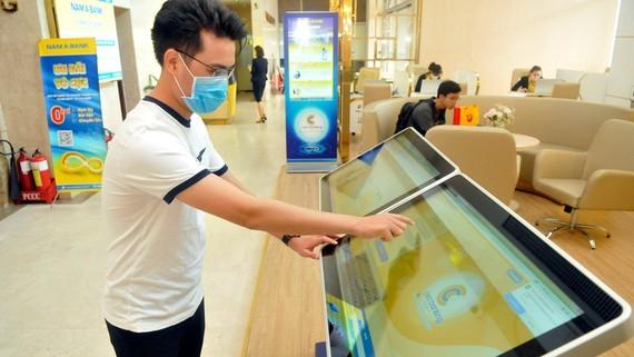 A customer uses banking services at Nam A Bank. (Photo: SGGP)