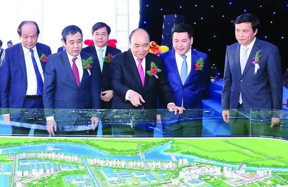 Prime Minister Nguyen Xuan Phuc and delegates watch the scale model of Lien Ha Thai Industrial Park - Thai Binh Economic Zone. (Photo: VNA)