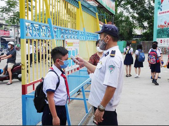 School security guard takes temperature of a student before he enters the school. (Photo: SGGP)