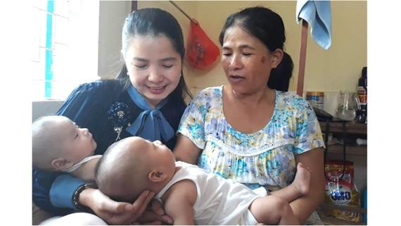 Nụ cười hạnh phúc của Lê Thị Thùy Na (bìa trái) bên cặp song sinh Thanh Bình và Tuấn Tú