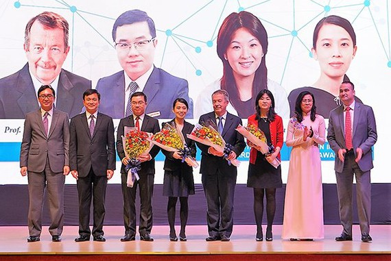 Vice Chairwoman of the municipal People's Committee Nguyen Thi Thu (in Ao Dai) congratulates scientists in the award ceremony. (Photo: Sggp)