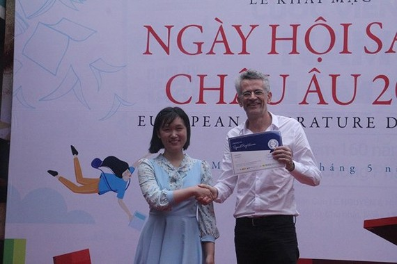 Ambassador Bruno Angelet, Head of the Delegation of the European Union to Vietnam presents a Certificate of Merit to Ly Thuy Vy, one of the winners of a painting competition themed Creative with European Literary Characters. (Photo: Sggp)