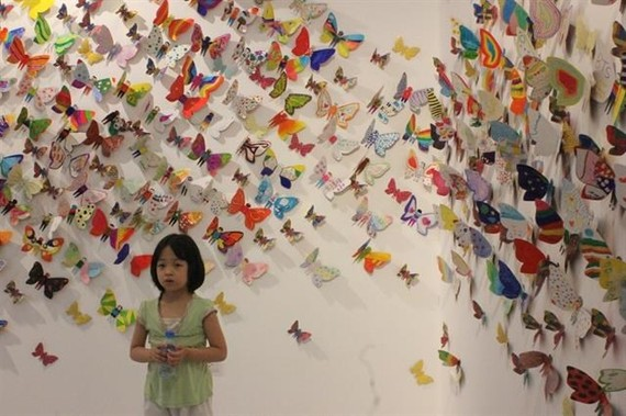 Little girl takes a photo with hundreds of colourful butterflies. (Source: VNA)