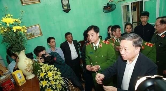 Minister of Public Security General To Lam burn incense in memory of Col. Nguyen Huy Thinh, one of the three police officers who died while performing their duty in Dong Tam commune, Hanoi's suburban district of My Duc. (Photo: VNA)