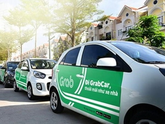 Cars which provide passenger transportation via ride-hailing platforms like Grab will have to put on top TAXI sign or carry logo stickers showing that they are contract vehicles. (Photo: VNA)