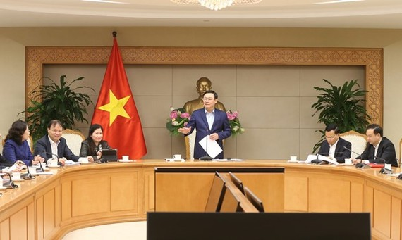 Deputy Prime Minister Vuong Dinh Hue (standing) addresses the meeting of the steering committee for pricing on January 31 (Photo: VNA)