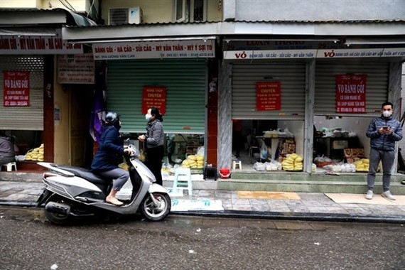 Stores on Hanoi's Luong Van Can Street half close their doors, only serve take-aways or online orders due to the impact of COVID-19 (Photo: VNA)