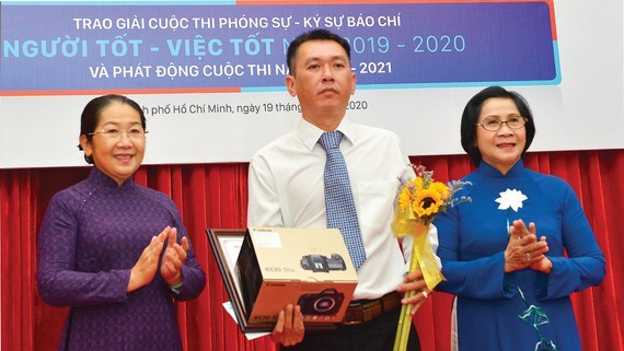 Former deputySecretaryof the HCMC Party Committee, Nguyen Thi Thu Ha (R ); Vice Secretaryof the municipal Party Committee, Vo Thi Dung (L ) award the first prize to journalist Minh Anh.