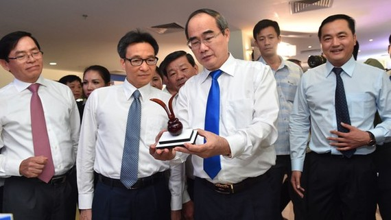 Secretary of Ho Chi Minh City Party Committee Nguyen Thien Nhan ( R ) and Deputy Prime Minister Vu Duc Dam see a souvenir craft product in a exhibition. (Photo: SGGP)